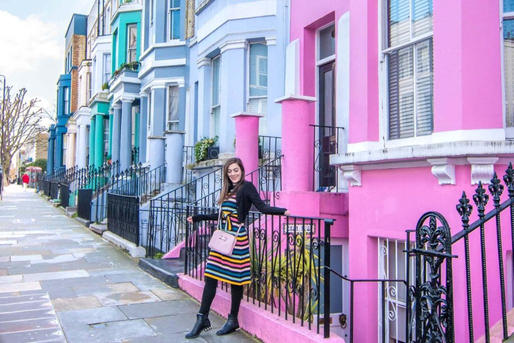 Girl standing in front of colorful houses on Westbourne Park Road in London