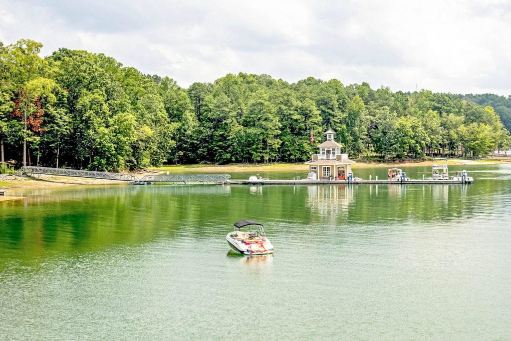 View of Lake Lanier with a boat on the water and boats at a dock.