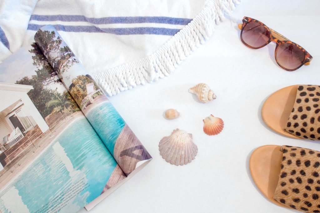 Flat lay of Aruba packing list with shells, sunglasses, sandals, and a beach blanket