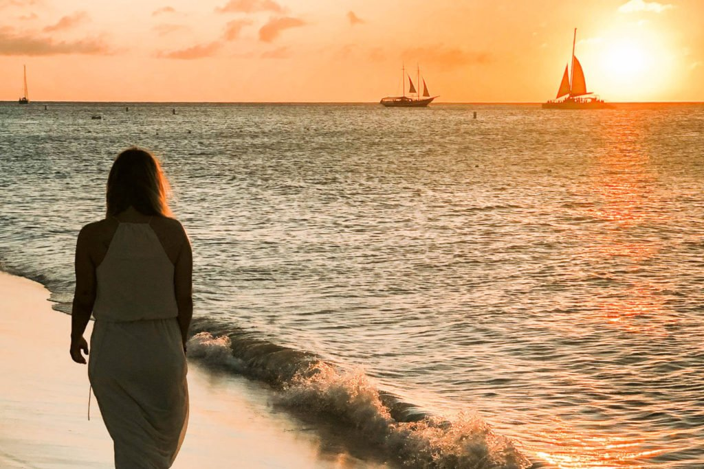 Woman walking on beach in Aruba as the sun sets