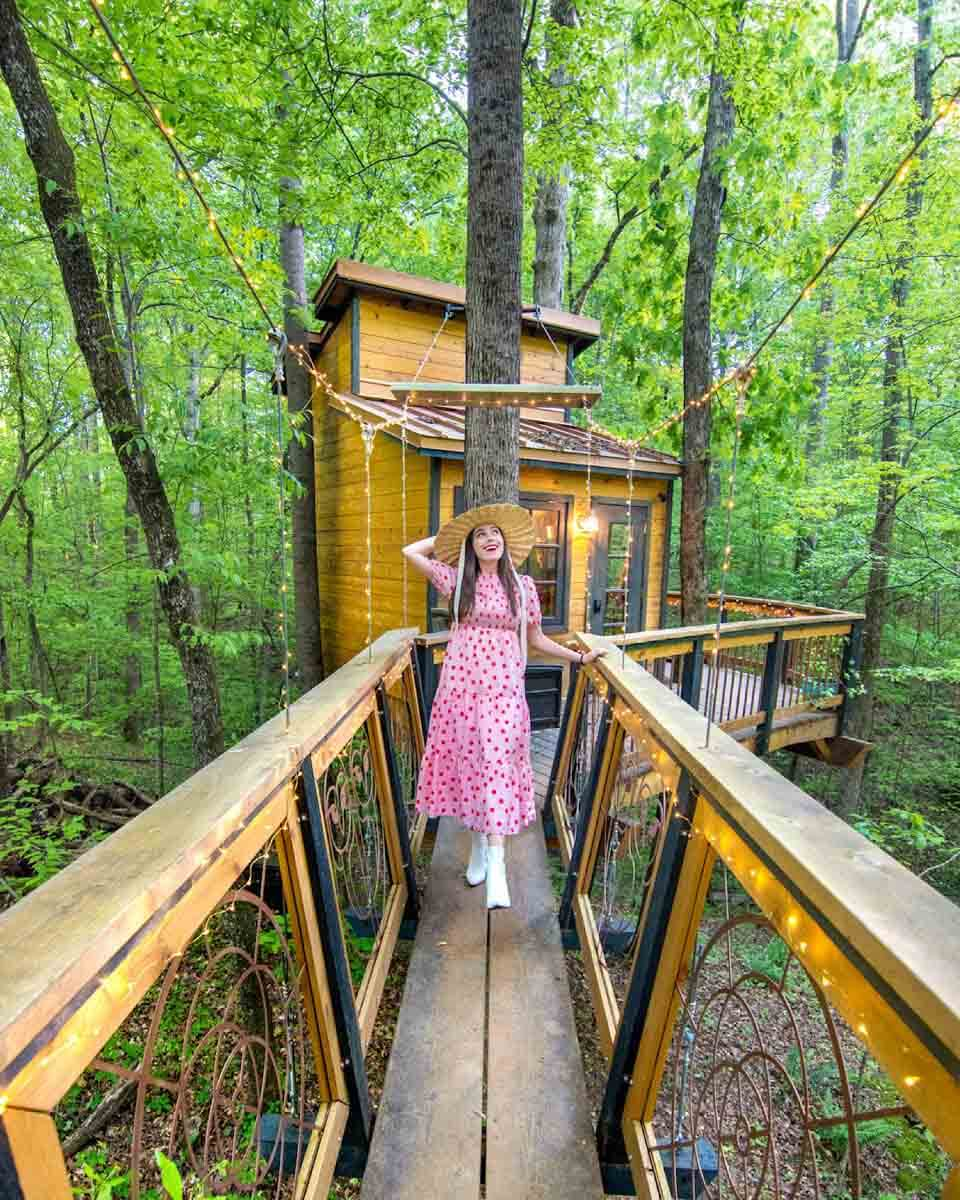 Woman standing on platform in front of Owl in the Oak treehouse