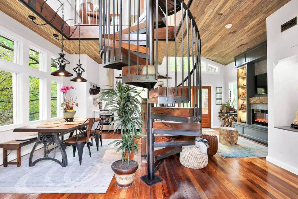 Photo of the inside of Archimedes' Nest Treehouse in Atlanta, showing a spiral staircase and living room area