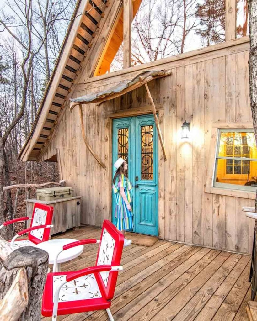 Woman standing at front door of Bed + Bough treehouse on the deck