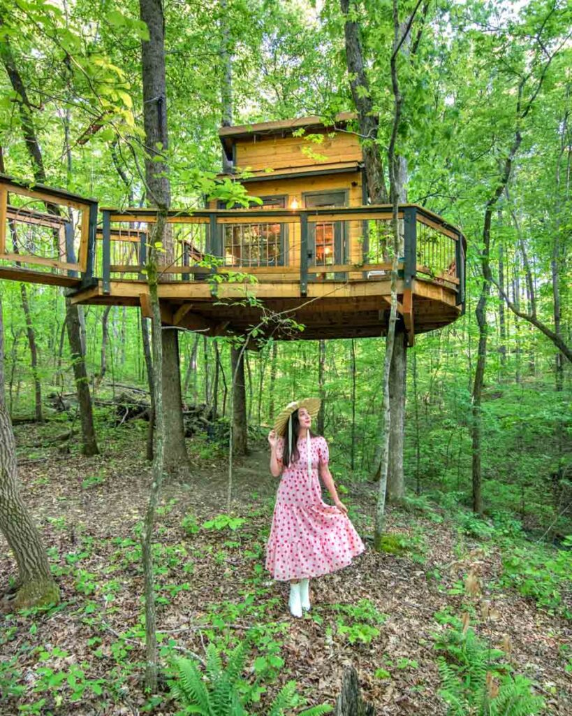 Woman in pink dress standing in front of Owl in the Oak Treehouse in Duluth, Georgia