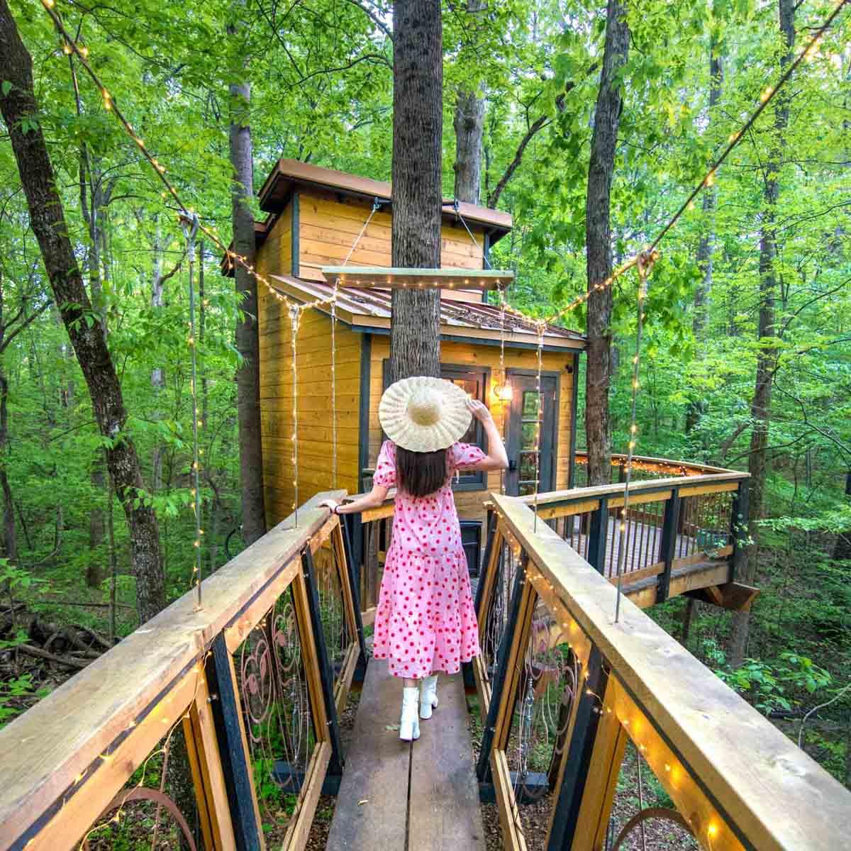 Woman walking in front of Owl in the Oak Treehouse near Atlanta, Georgia
