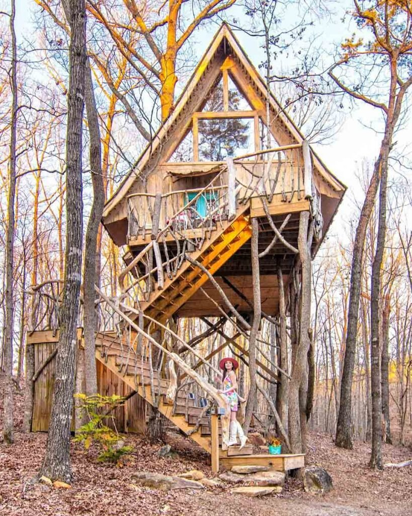 Woman standing on front of Bed+Bough Treehouse during the winter