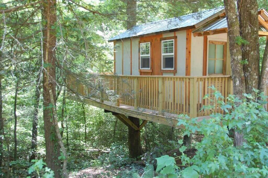 Photo of the side of Cozy Treehouse in Helen, showing the porch and surrounding forest