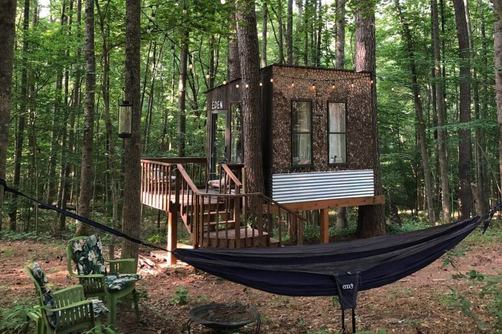 View of Eden Treehouse in Canton, GA, showing treehouse and outdoor sitting area with hammock