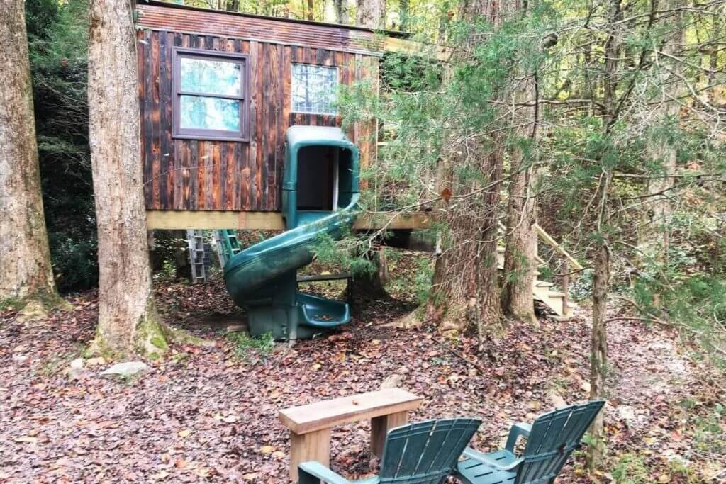 Front view of Kaluna Farm Retreat Treehouse in Talking Rock, showing a slide and sitting area