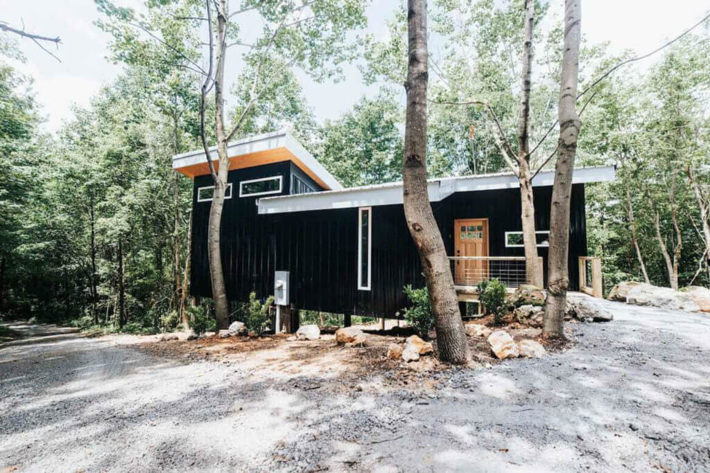 Front view of this black treehouse surrounded by forest