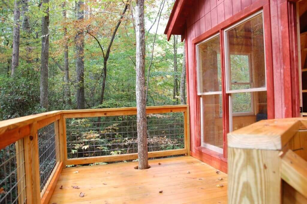 View of side porch at this secluded treehouse near Helen, Georgia, showing the surrounding forest