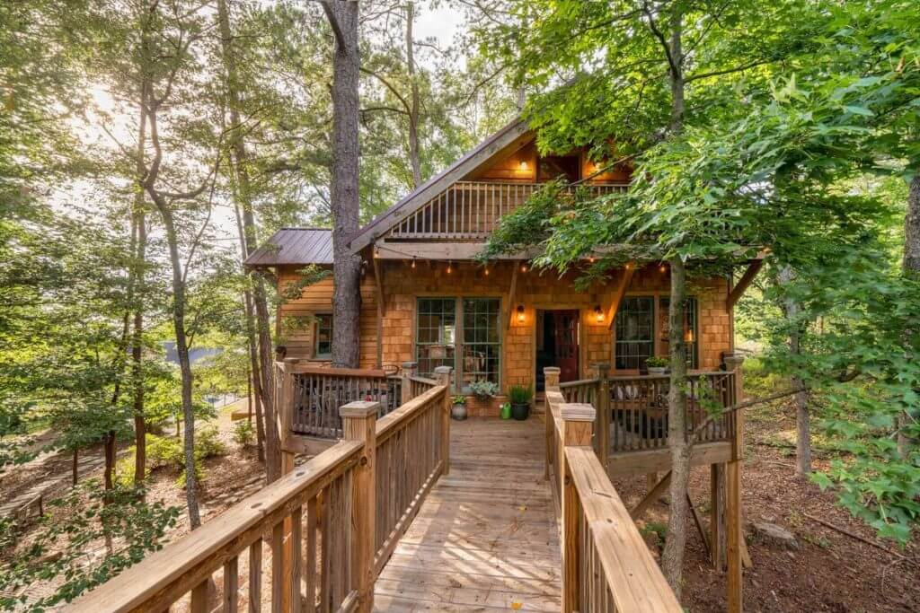Front view of Trinity Treehouse in Stonecrest, showing walkway, entrance, and surrounding forest