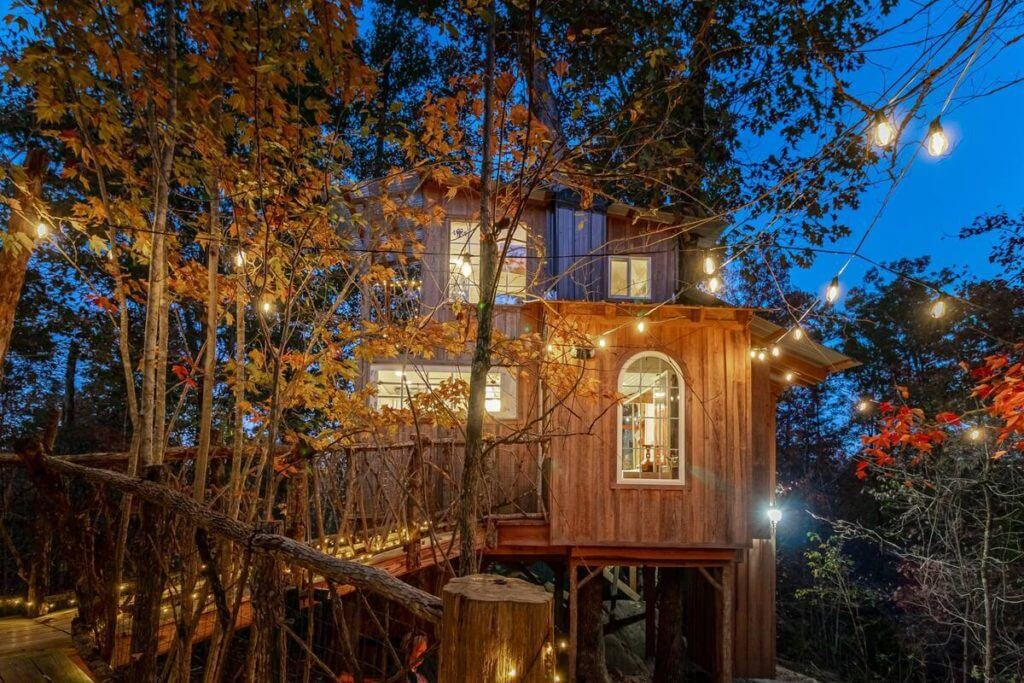 View of Whippoorwill Retreat Treehouse in Georgia lit up at night during the fall