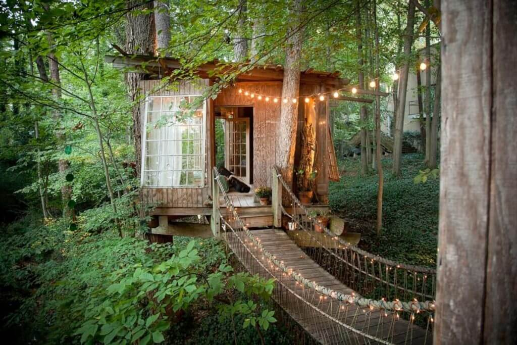 Front view of the most popular treehouse on Airbnb in Atlanta, showing suspended walkway and string lights lighting up bedroom
