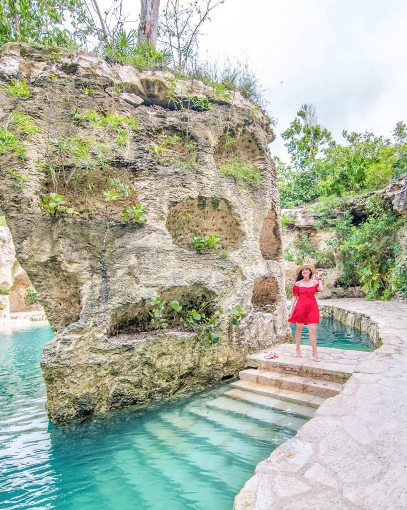 Girl walking around landscape of Hotel Xcaret Mexico by water