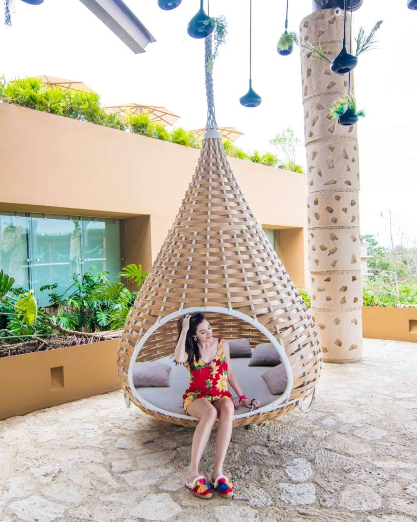Girl sitting in hanging swing of lobby at Hotel Xcaret Mexico