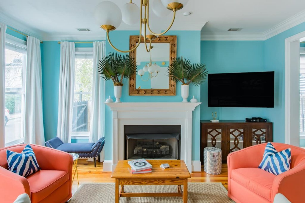 View of living room in the Bright and Sophisticated Home in Historic District listing, with orange chairs and bright blue wall