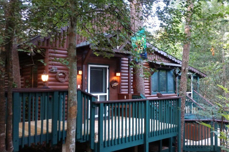 View of the front façade of the treehouse cabin, with a porch and walkway