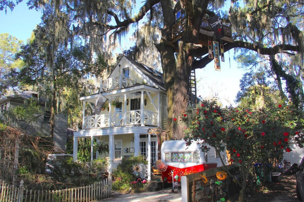 Photo of the outside of the Diamond Oaks home, showing the front of the house, the treehouse, and a campervan