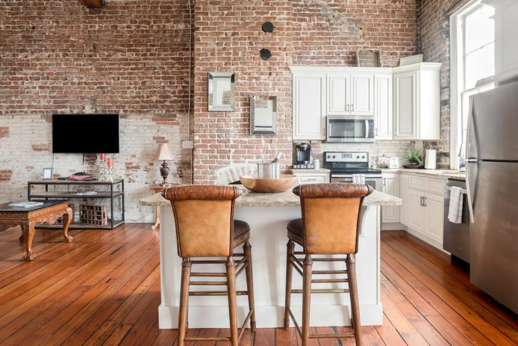 Photo of the open kitchen with brick walls in the Downtown Riverfront Condo With Industrial Accents listing on Airbnb