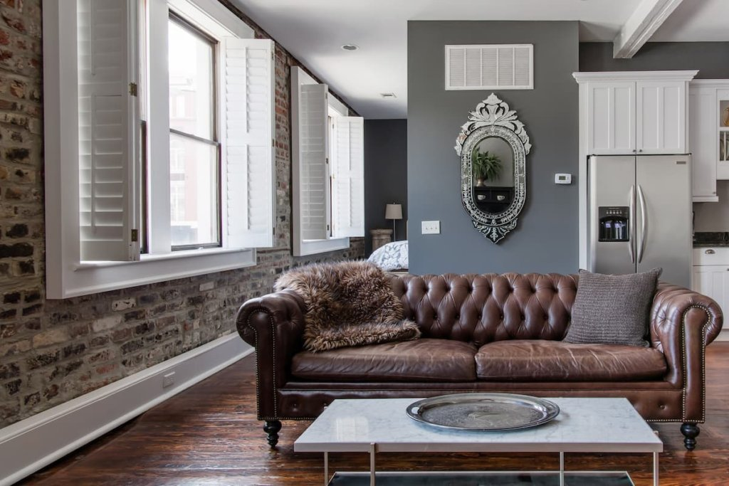 Photo of the sitting area, with brick wall and comfy leather couch in Ellis Square Place listing on Airbnb