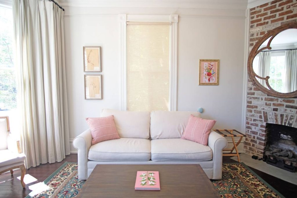 Photo of the white couch with pink pillows in the Leland Suite