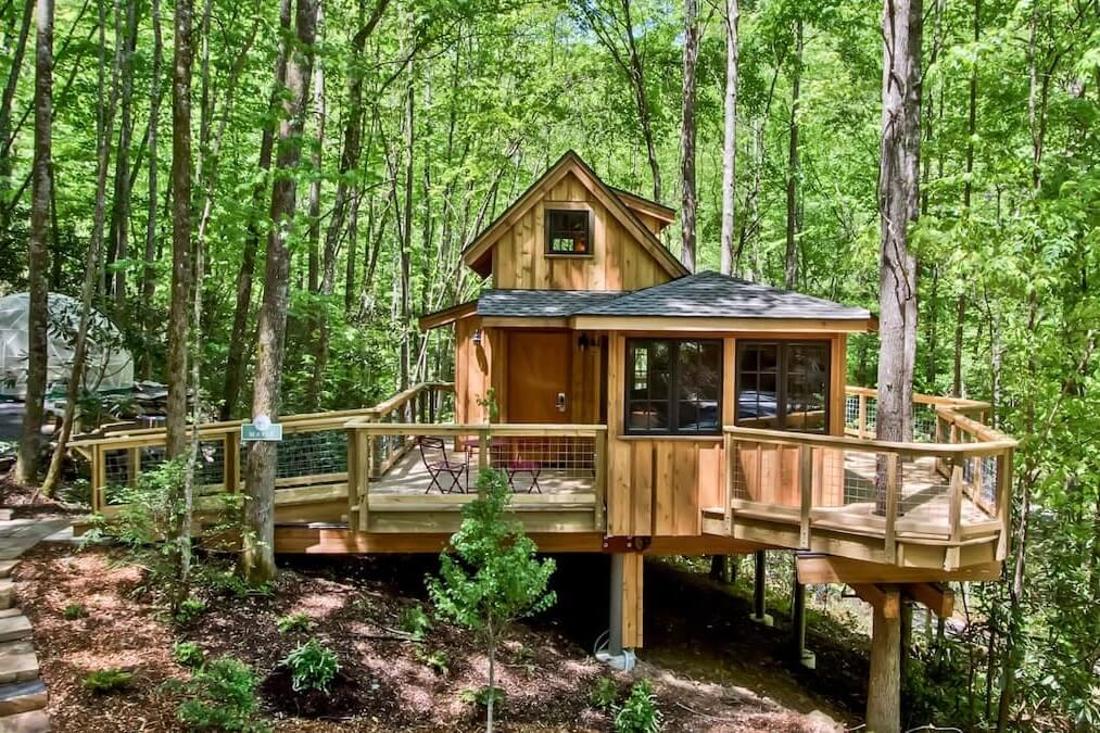 Photo of the front of The Maple in Treehouse Grove at Norton Creek, showing its wraparound porch and separate yurt