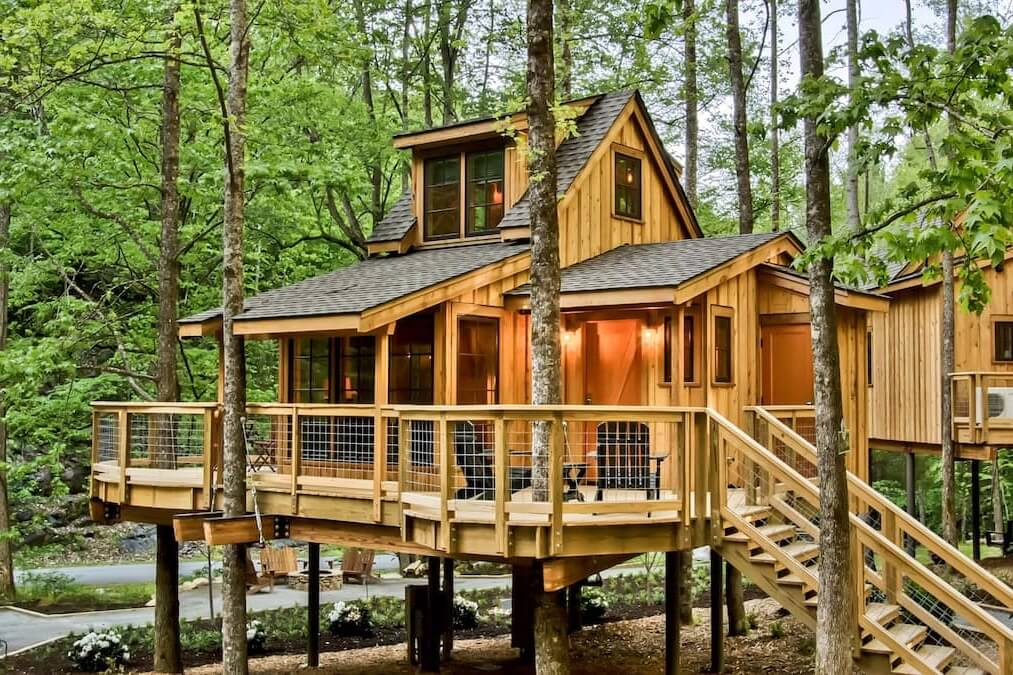 Photo of The Poplar in Treehouse Grove at Norton Creek, showing its façade, front porch, and steps to reach the treehouse