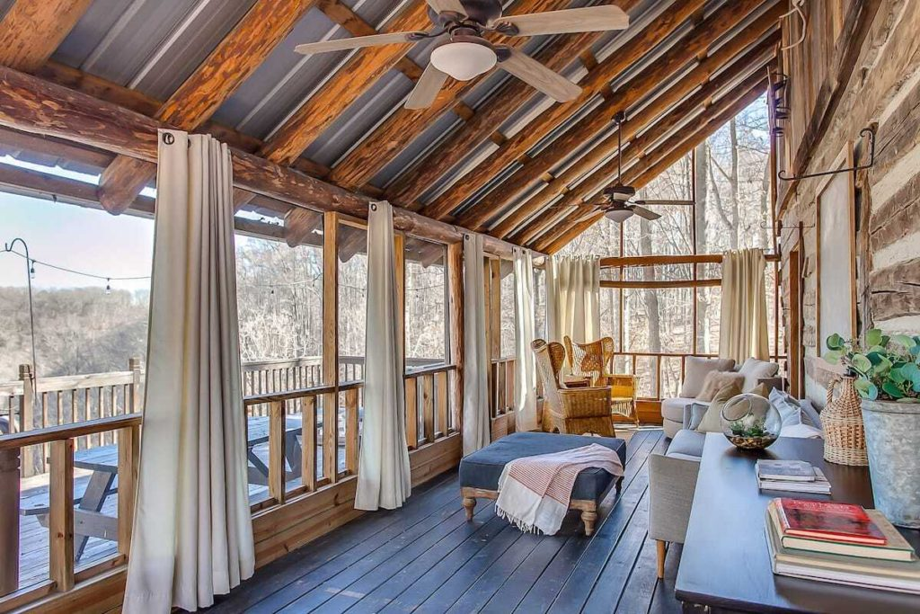 Photo of the screened-in porch in one of the pioneer cabins, with beautiful views of the lake and surrounding trees