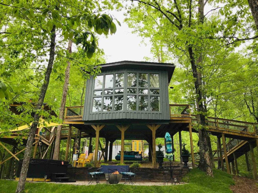 Photo of the façade of Sulfur Ridge luxury treehouse, with a sitting area below