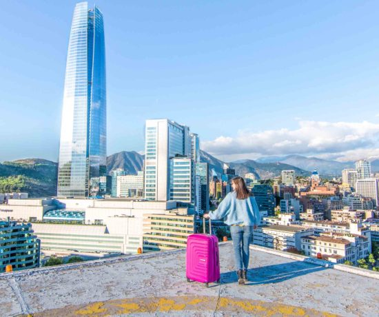 Girl with suitcase standing on roof of building, with Gran Torre Santiago and a view of the Santiago skyline in the background
