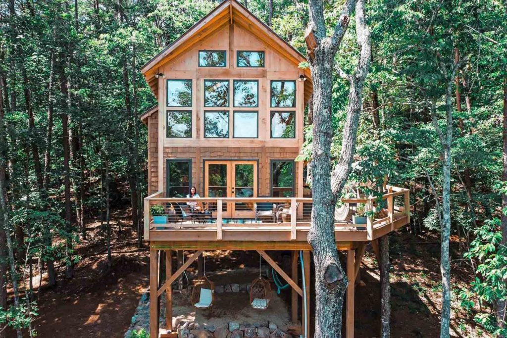 Photo of the façade of the Daybreak Treehouse in Dahlonega, surrounded by trees