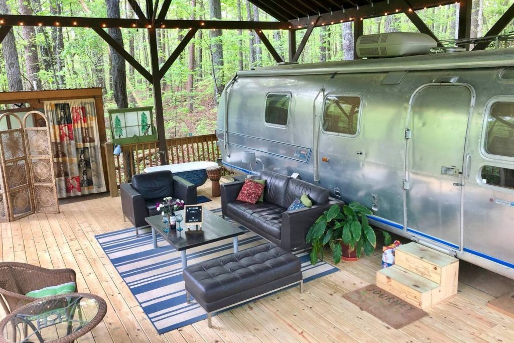 Photo of the outside of vintage camper with a seating area set up