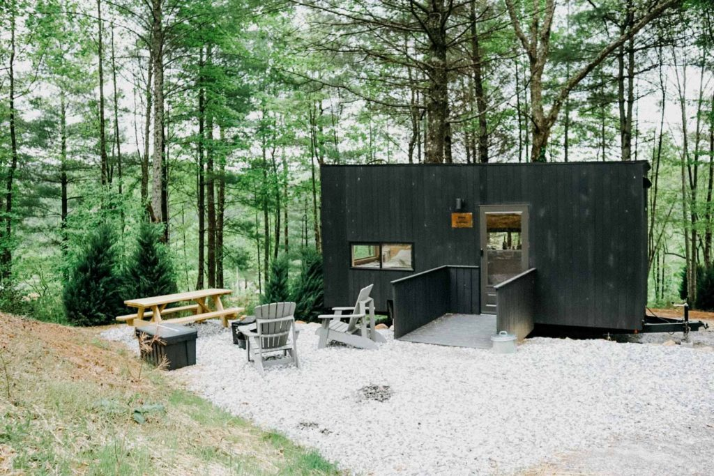 Photo showing the outside of Getaway House Chattahoochee, featuring black tiny cabin and an outdoor seating area
