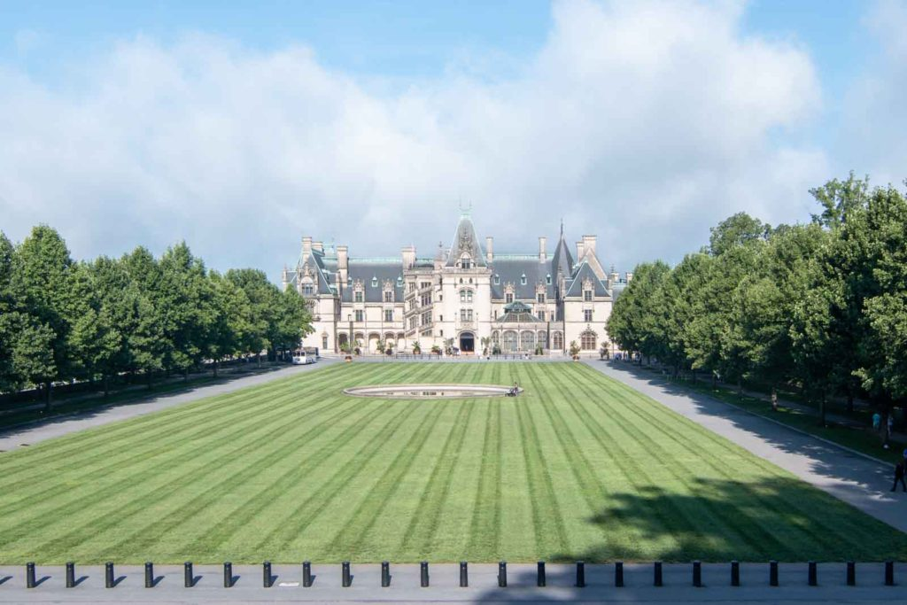 A view of the front of the Biltmore House, showing the large lawn leading up to the house.