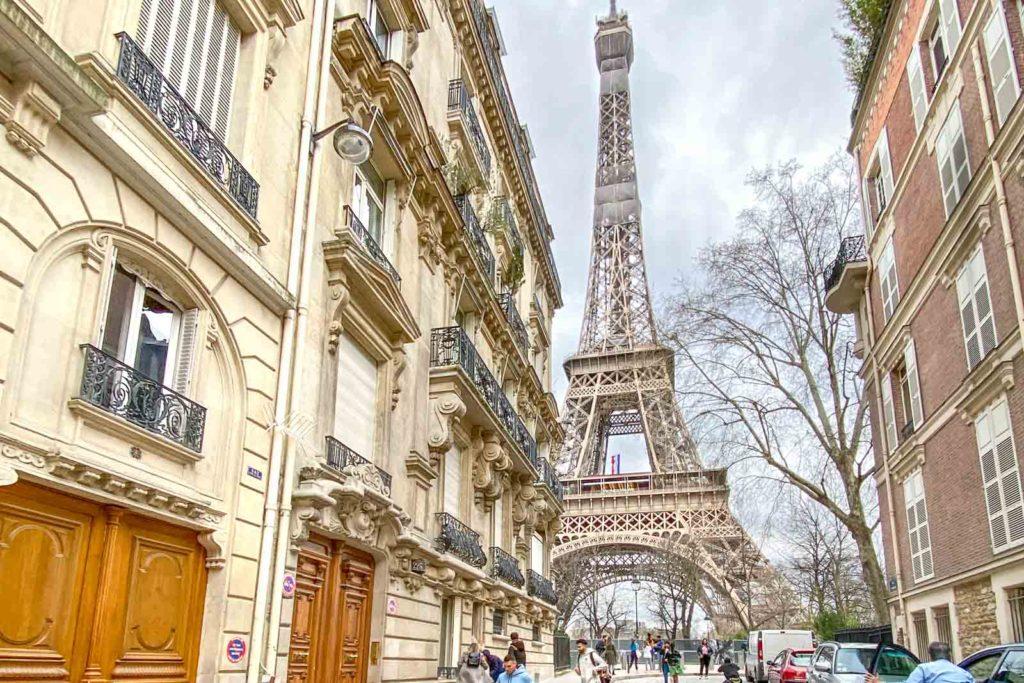 Photo of Rue de l'Université in Paris, showing the Eiffel Tower next to two buildings.