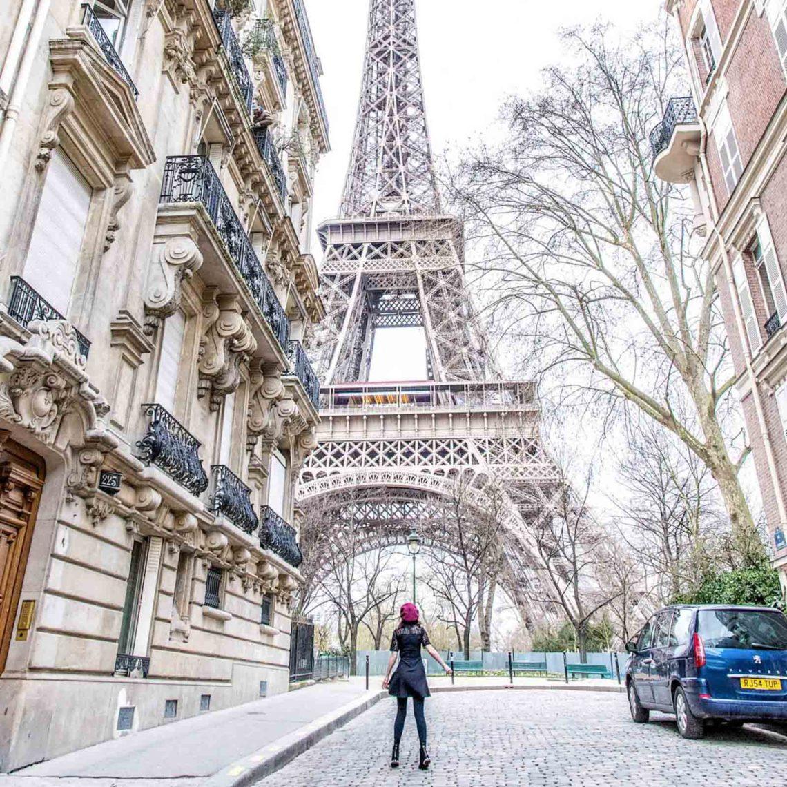 Woman standing in front of Eiffel Tower on Rue de l'Université in Paris.