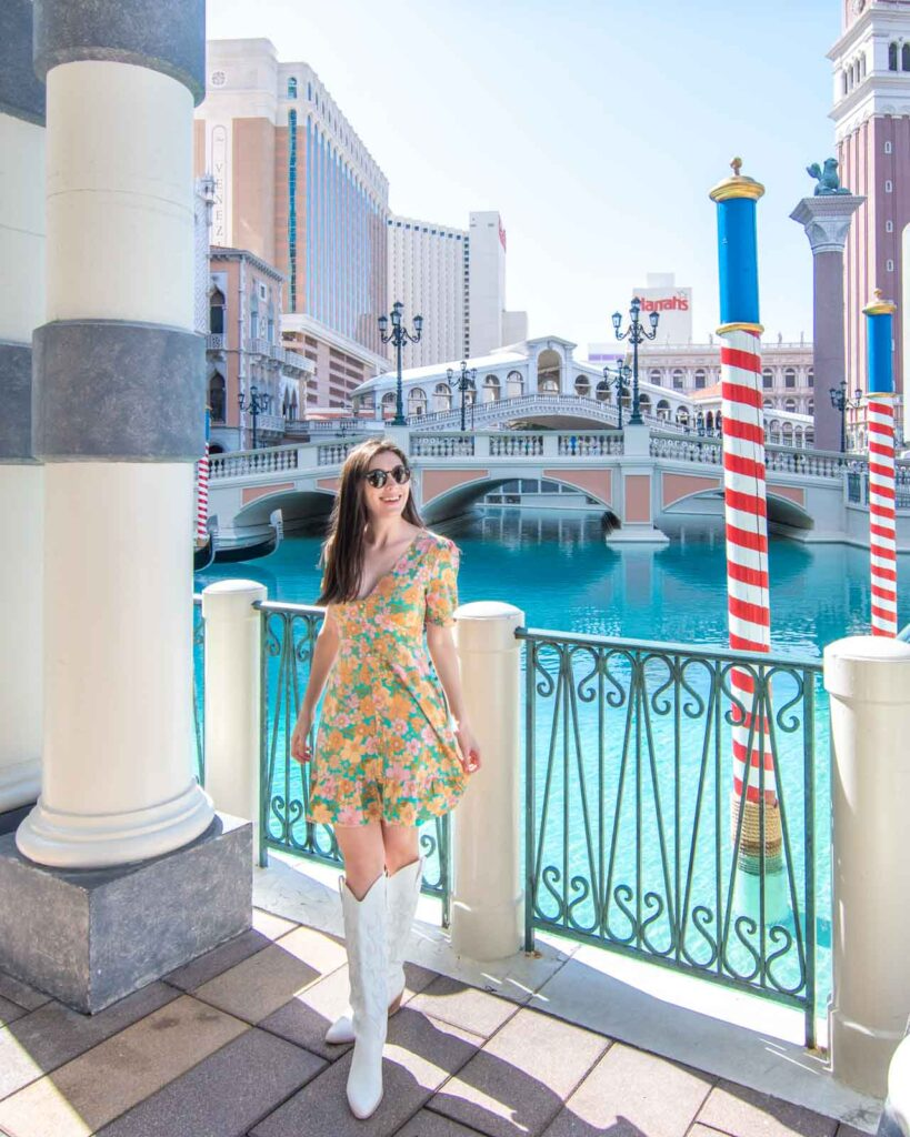 Woman standing in front of the canals and outdoor gondola rides at the Venetian Las Vegas