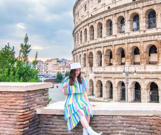 Woman sitting on ledge in front of the Colosseum in Rome