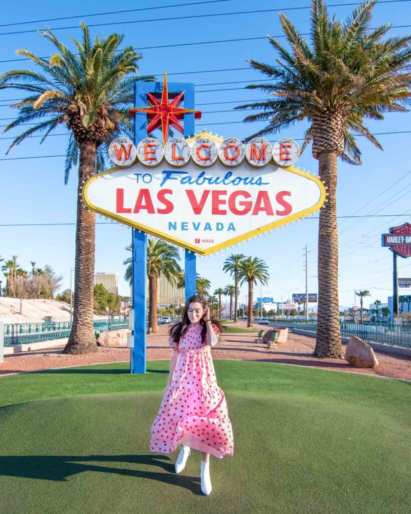 Woman in pink dress walking in front of Welcome to Fabulous Las Vegas sign