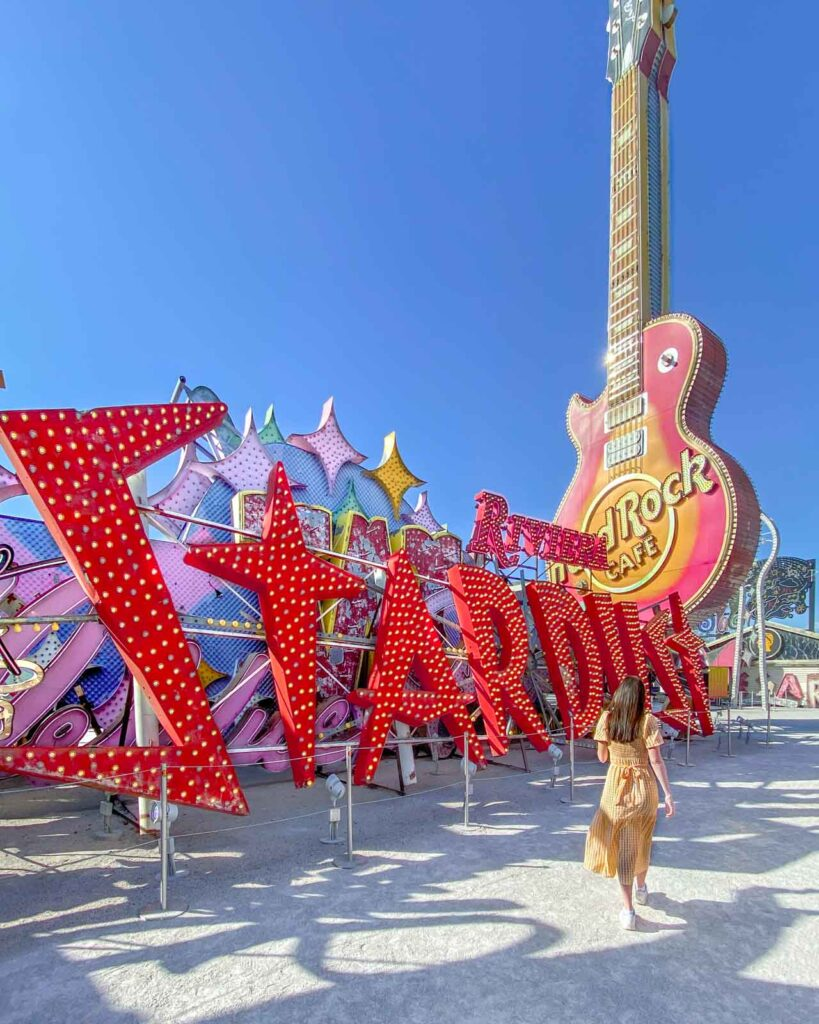 Woman with back to camera walking through the Neon Museum next to Stardust sign