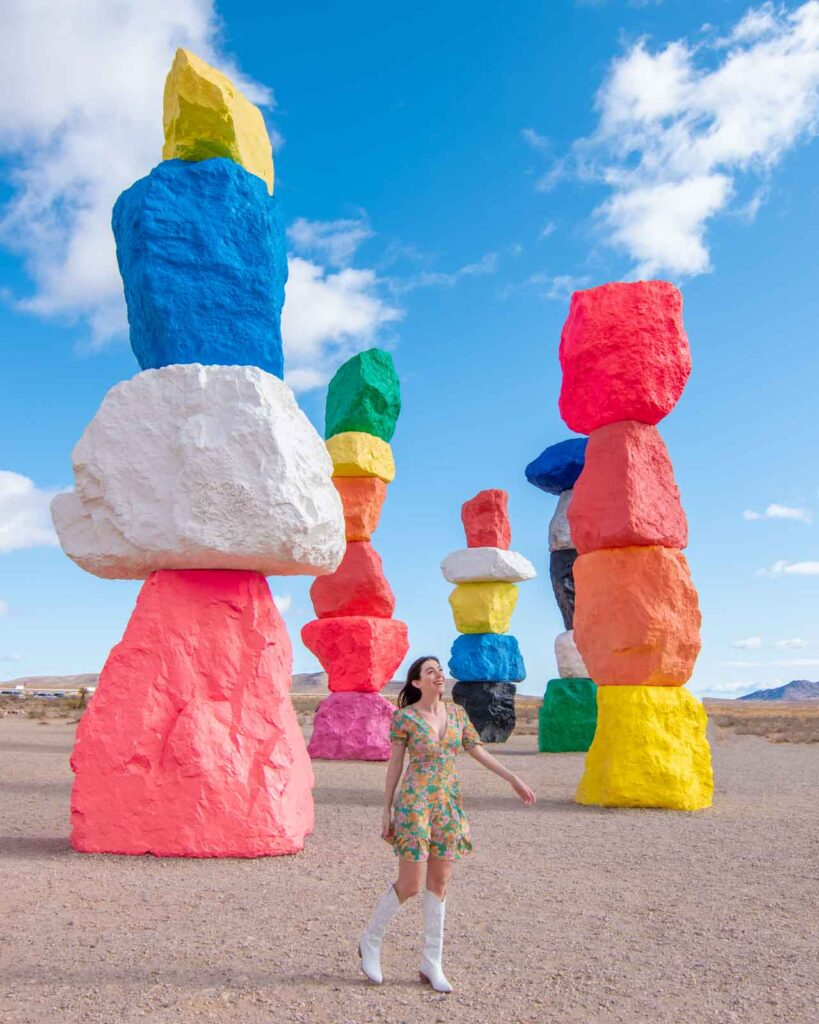 Woman walking in front of painted totems at Seven Magic Mountains