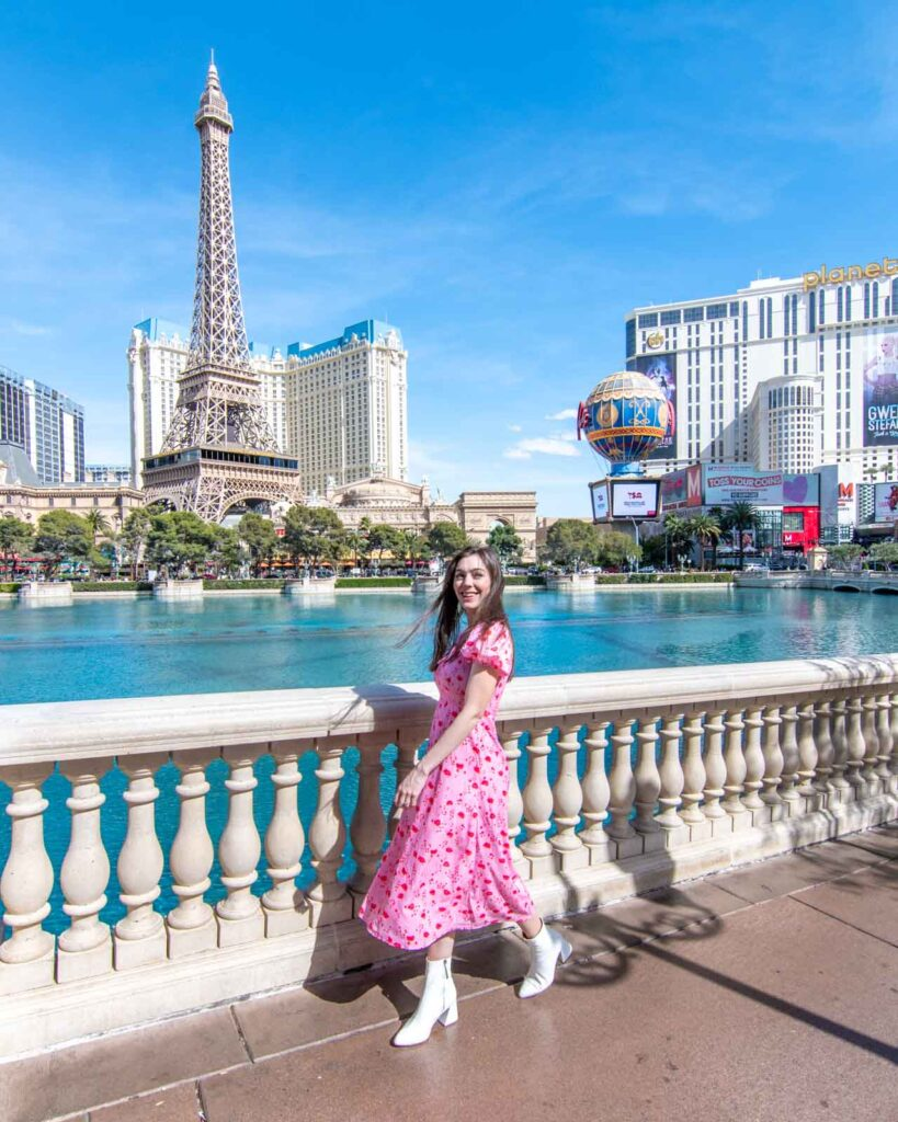 Woman in pink dress walking in front of the Bellagio with the Paris Las Vegas Eiffel Tower in the background