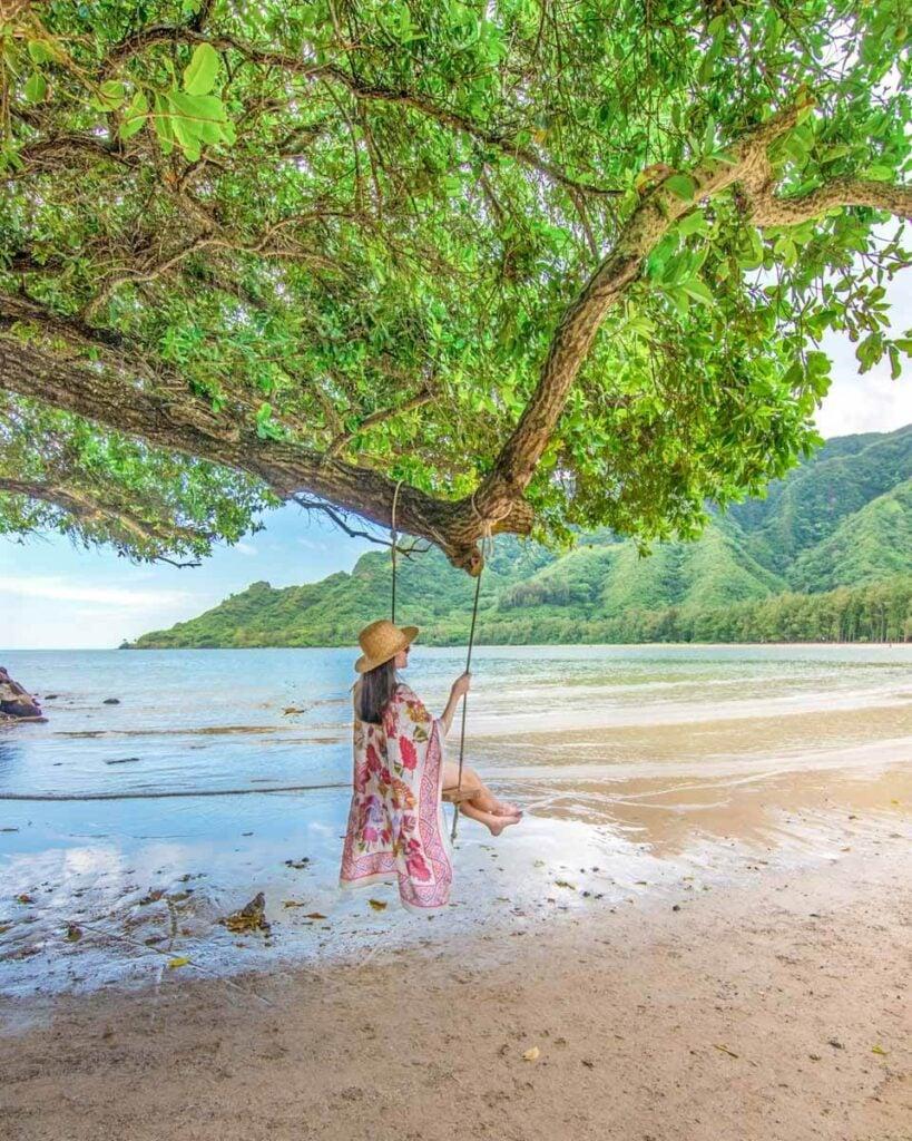 Woman swinging on beach swing on Oahu, Hawaii