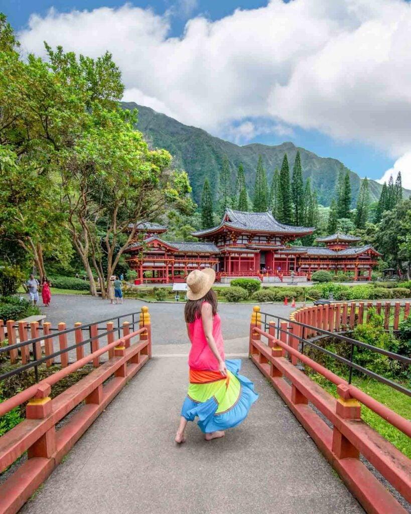 Woman walking in front of The Byodo-In Temple across bridge