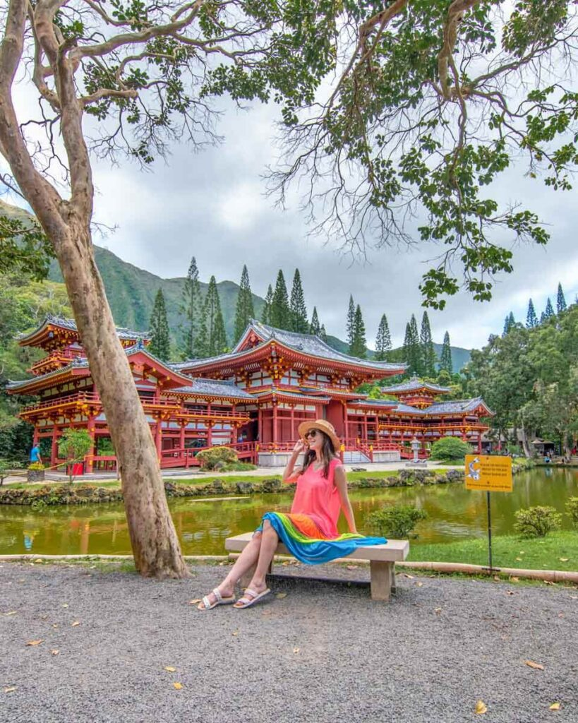 Woman sitting on bench in front of The Byodo-In Temple