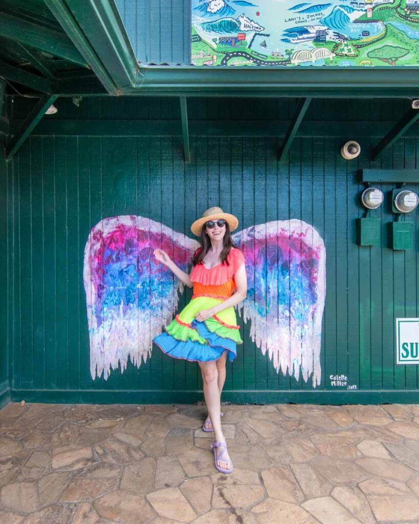 Woman in front of wings mural in Haleiwa Town on the North Shore, Oahu