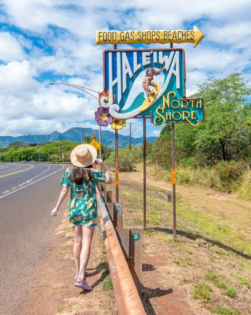 Woman standing next to Haleiwa surfer sign on the North Shore