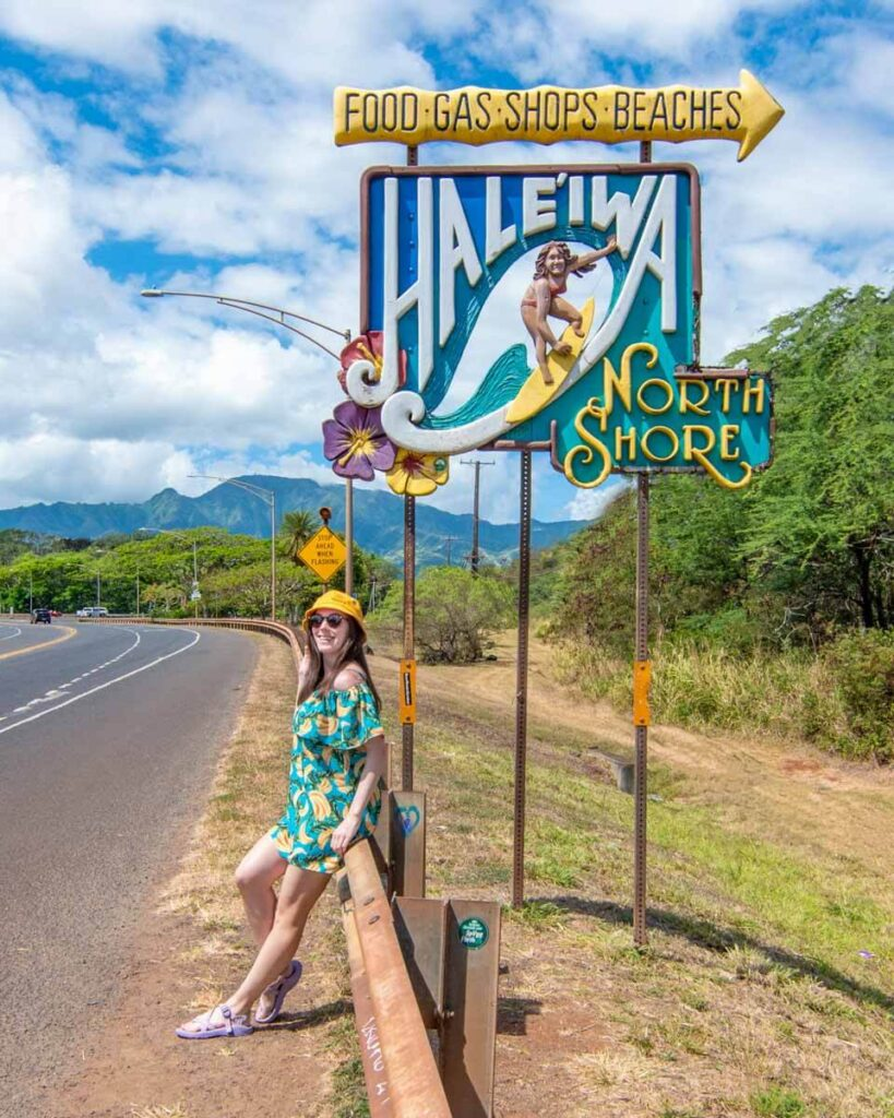 Woman leaning against Haleiwa surfer sign on North Shore, Oahu