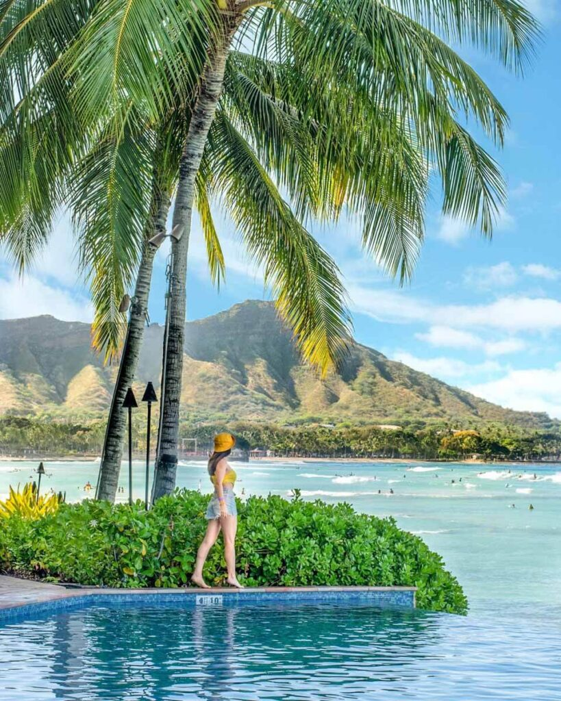 Woman walking next to infinity pool at the Sheraton Waikiki with Diamond Head in the distance